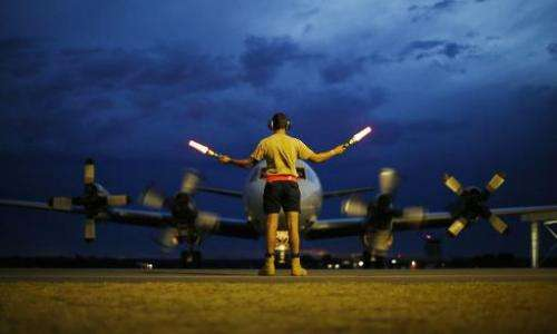 A ground controller guides a Royal Australian Air Force AP-3C Orion to rest a search for flight MH370 over the Indian Ocean