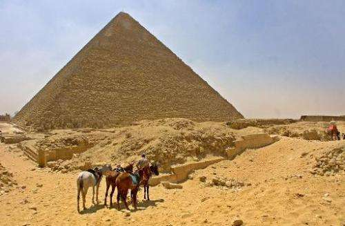 A horseman waits with his horses for tourists in front of Egypt's Cheops Pyramid at Giza plateau south of Cairo 13 June 2002