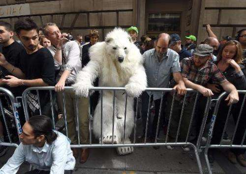 "A man dressed as a polar bear climbs a barricade as protestors take part in the ""Flood Wall Street"" demonstrations on"