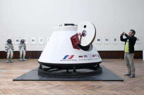 A man takes a picture of the Soviet space capsule Vozvrashchayemi, on May 5, 2014, in Brussels