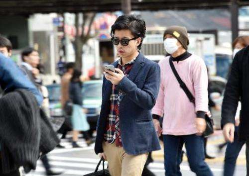 A pedestrian using his smartphone on a street in Tokyo, November 3, 2014. Growing ranks of cellphone addicts are turning cities