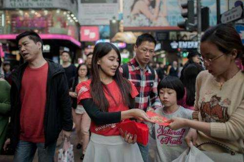 A public relations woman distributes lai see packets filled with bitcoin coupons to pedestrians to mark the Chinese New Year in