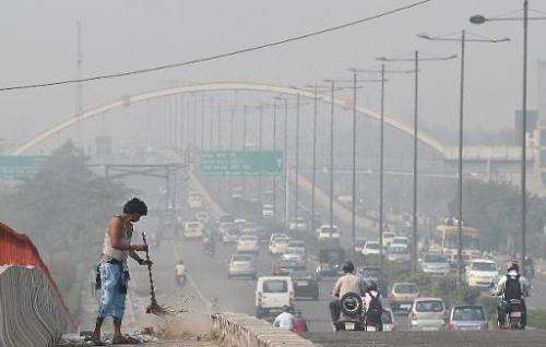 A sweeper cleans a flyover as smog covers the capital's skyline in New Delhi on October 24, 2014