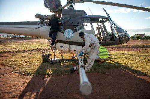 A team prepares a helicopter equipped with pesticide-spreading equipment to fight a locust plague in Tsiroanomandidy, Madagascar