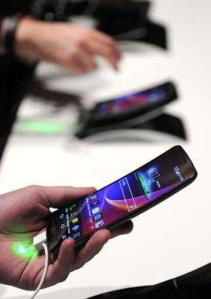 Attendees look at LG's new G Flex curved screen smartphone, at the LG press conference at the Mandalay Bay Convention Center for