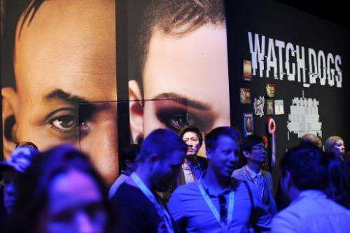"Attendees walk by the display for the Ubisoft game ""Watch Dogs"" at the E3 video game trade show in Los Angeles on June"