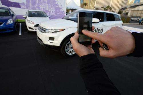 A Valeo representative swipes his finger across an iPhone to initiate a self parking demonstration at the International CES in L