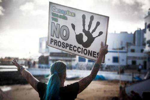 """A woman holds a placard reading """"Canaries, only one voice: No prospections"""" as she invites tourists to take part in th"""
