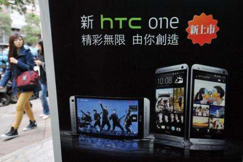 A woman walks past HTC advertising in Taipei on May 2, 2013