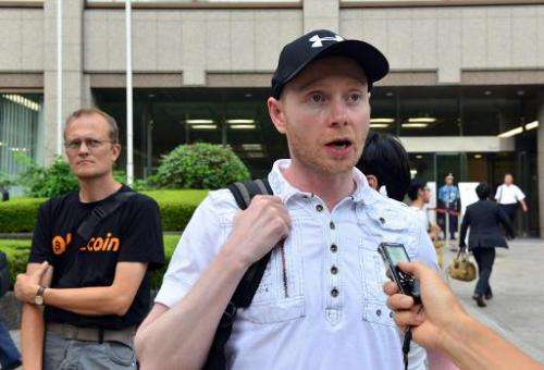 Bitcoin trader Kolin Burges from Britain speaks to a reporter after he attended the first creditors' meeting of failed Bitcoin e