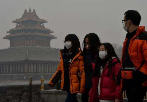 Chinese tourists wear face masks while walking past the Forbidden City as heavy air pollution shrouds Beijing on February 26, 20