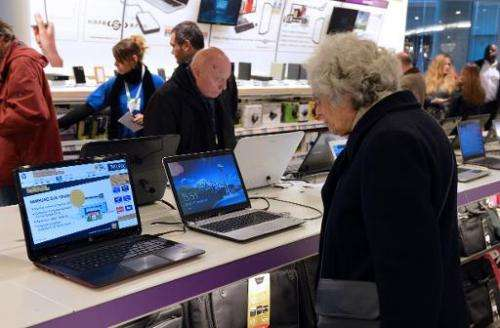 Customers look at computers displayed at a FNAC store on November 27, 2012 in Paris