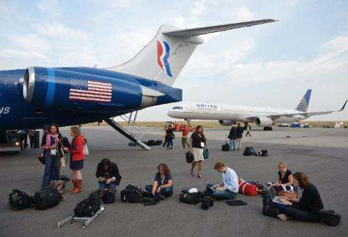 Journalists work on laptops next to Mitt Romney's campaign plane, at Denver International Airport, on September 23, 2012