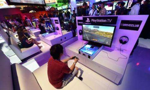 A file picture taken in Los Angeles, California on June 10, 2014 shows people testing the new Playstation consoles at the annual