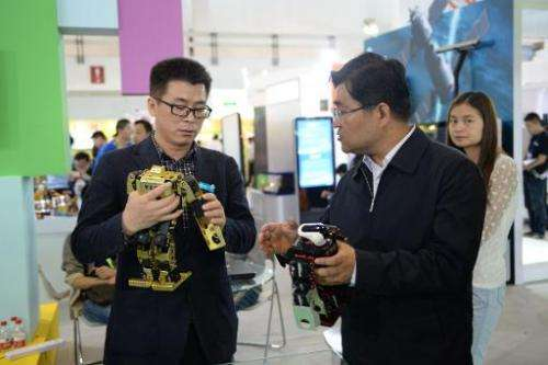 This picture taken on May 14, 2014 shows visitors playing with robots during the 17th China Beijing International High-Tech Expo