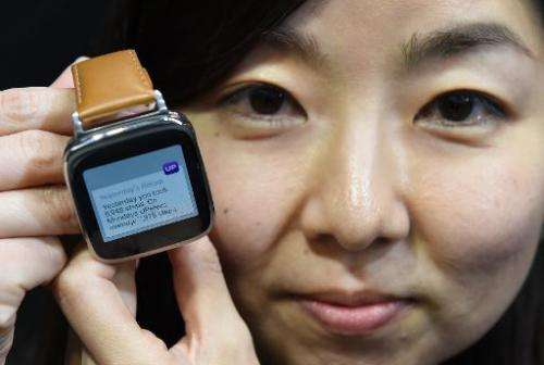 An employee of Taiwan's ASUS TeK Computer shows its new smartwatch during a press conference in Tokyo, on October 28, 2014