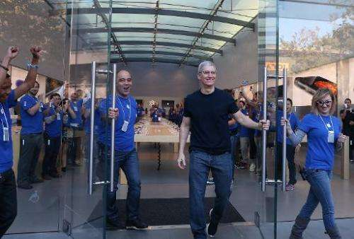 Apple CEO Tim Cook (R) opens the door to an Apple Store to begin sales of the new iPhone 6 on September 19, 2014 in Palo Alto, C