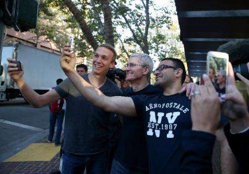 Apple CEO Tim Cook (C) takes a selfie photo with people waiting in line to buy the new iPhone 6 at an Apple Store on September 1