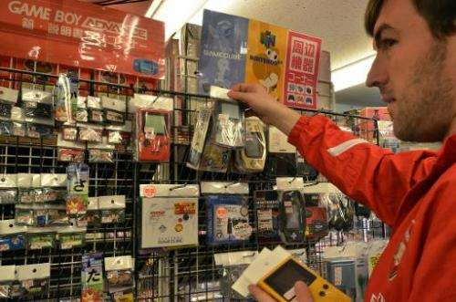 A customer checks out used Game Boy consoles a videogame shop in Tokyo, on April 17, 2014