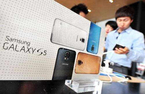 A customer looks at Samsung's Galaxy S5 smartphone at a mobile phone shop in Seoul on March 27, 2014
