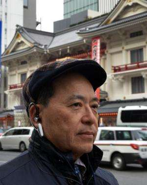 An engineer of Japanese machinery maker NS West wears the 'Earclip-type Wearable PC', equipped with vital sensors such as pulse