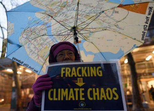 A woman holds an anti-fracking sign at a rally for a Global Climate Treaty December 10, 2014 near the United Nations in New York