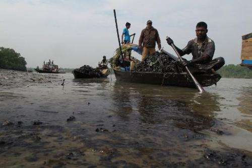 Bangladeshi villagers collect oil from their skiff in the Shela River in Mongla on December 13, 2014, after an oil-tanker carryi