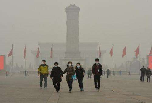 Chinese tourists wearing facemasks during a visit to Tiananmen Square as heavy air pollution continues to shroud Beijing, on Feb