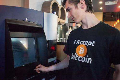 File photo taken on October 29, 2013 shows a man using the world's first bitcoin ATM at Waves Coffee House in Vancouver, Canada