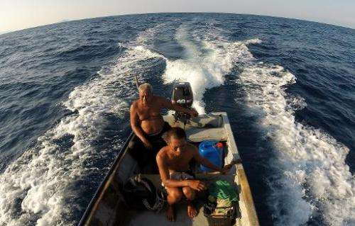 Fish listener Harun Muhammad (L) mans his fishing boat at sea near Setiu lagoons with his son Zuraini on June 8, 2014