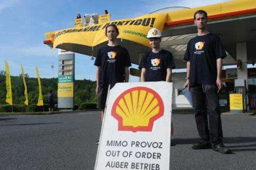 Greenpeace activists stage a protest on May 10, 2012 at a Shell petrol station in Prague