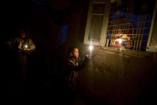 In this file photo, a Palestinian woman and her children light candles during a power outage in Gaza City, on November 10, 2013