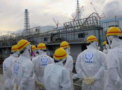 Members of the International Atomic Energy Agency inspect a spent fuel pool at the crippled Tokyo Electric Power Fukushima nucle