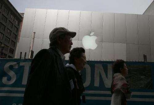 Pedestrians walk by an Apple Store on July 10, 2013 in San Francisco, California