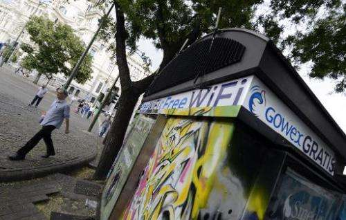 People walk past a kiosk with an advertisement for wifi provider Gowex in Madrid, on July 3, 2014