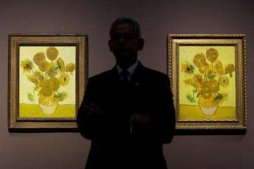 A file photo taken on January 24, 2014 shows a gallery supervisor posing in front of two versions of Dutch artist Vincent van Go