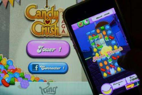 A man plays at Candy Crush Saga on his iPhone in Rome on January 25, 2014