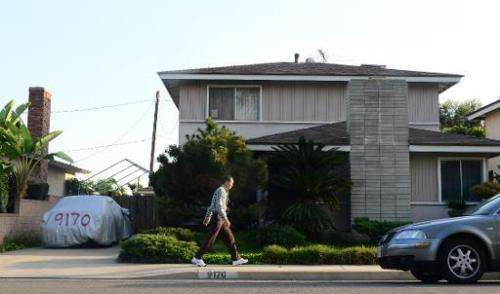 """A man walks past the reported home of """"Satoshi Nakamoto"""" in Temple City, east of Los Angeles, California on March 6, 2"""