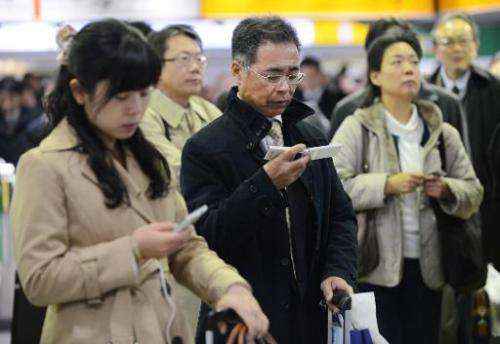 People look at their mobile phones to check updated information on possible rail line suspensions following a powerful 7.3 under