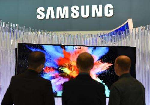 Visitors look at a curved TV set, displayed at the booth of South Korean electronic giant Samsung, during the consumer electroni