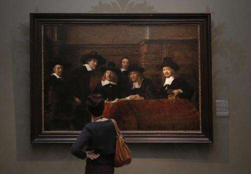 "A visitor looks at a work by Dutch artist Rembrandt Harmensz van Rijn entitled ""The Syndics of the Amsterdam drapers' Guild"