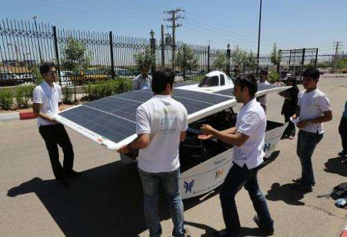 Iranian students from Qazvin Azad Islamic University assemble the solar-powered Havin-2 vehicle for a test drive in Qazvin on Ju