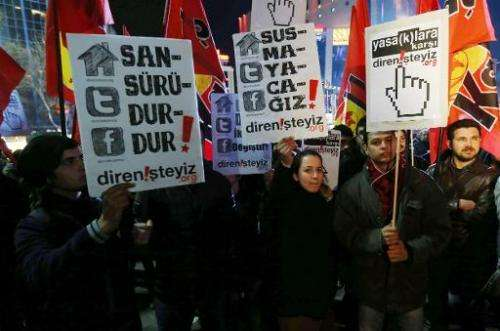 """Protesters hold a placard reading """"Stop the censorship!"""" as they demonstrate against new controls on the Internet appr"""