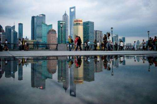 Pedestrians walk past the skyline of the city's financial district in Shanghai on October 8, 2010