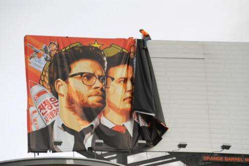 "Workers remove a poster-banner for ""The Interview"" from a billboard in Hollywood, California, December 18, 2014"