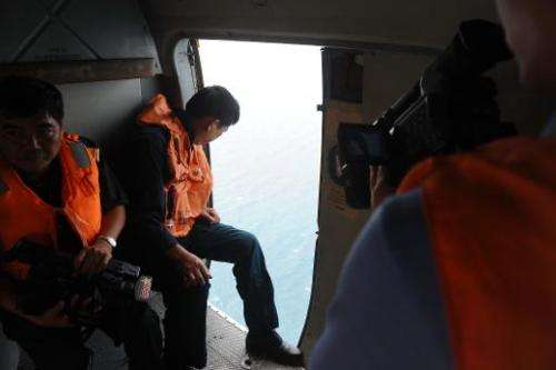 This picture taken aboard a Vietnamese Air Force's Russian-made MI-171 helicopter shows a crew member (C) looking out of a door