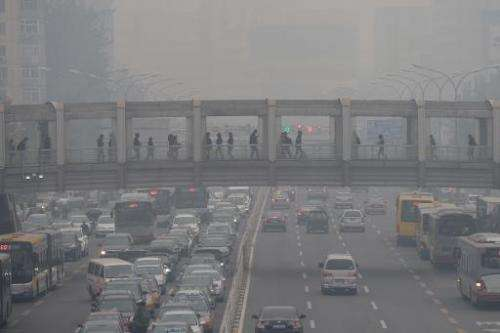 Pedestrians walk through an overpass as commuters drive on a road below in Beijing amid heavy smog, on October 8, 2014