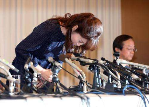 Haruko Obokata (L), a researcher at Japan's Riken Institute, bows as she apologises at a press conference in Osaka on April 9, 2