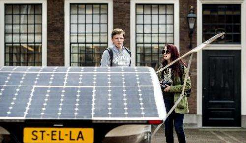 "A boy and a girl stand next to the Dutch solar-powered car ""Stella"" in front of the Binnenhof, the Dutch Parliament bu"