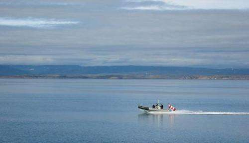 A Canadian Navy Zodiac races across the Arctic Ocean on patrol at the southern tip of Baffin Island, Canada, on August 09, 2007